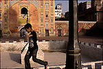 a young boy plays in the court yard of the wazir khan mosque in the old city of lahore