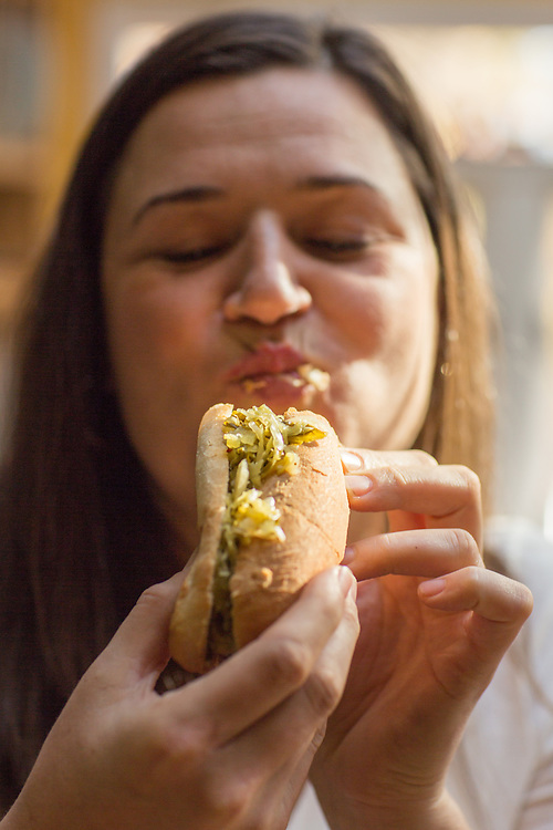 Hillsborough, North Carolina - Friday November 13, 2015 - April McGregor, founder of Farmer's Daughter, takes a bite of the bratwurst covered with her Collard Kraut.