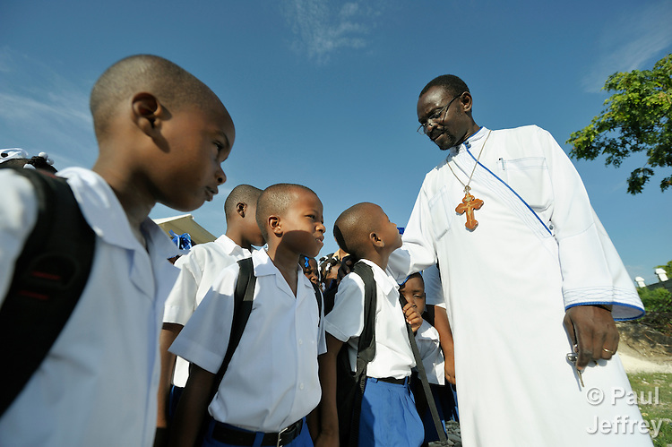 Father Jean-Chenier Dumais, a Russian Orthodox priest in Port-au-Prince, Haiti, welcomes children to the Notre Dame de Petits school at the beginning of a school day. The school's building collapsed in the January 2010 earthquake, and classes are currently conducted in the large tents in the background, provided by International Orthodox Christian Charities.