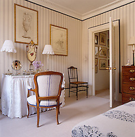A traditional dressing table draped in broderie anglaise against a wall covered in blue and white striped fabric in a guest bedroom