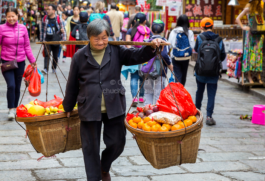 Yangshuo, China.  Woman Carrying Heavy Fruit Basket on Shoulder Pole.