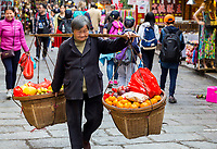 Yangshuo, China.  Woman Carrying Heavy Fruit Basket on Shoulder Pole.