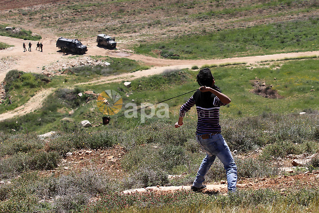 A Palestinian protester uses a slingshot to hurl stones toward Israeli security forces during clashes following a demonstration against Jewish settlements in the West Bank village of Qaryout near Nablus on April 01, 2016. Photo by Nedal Eshtayah