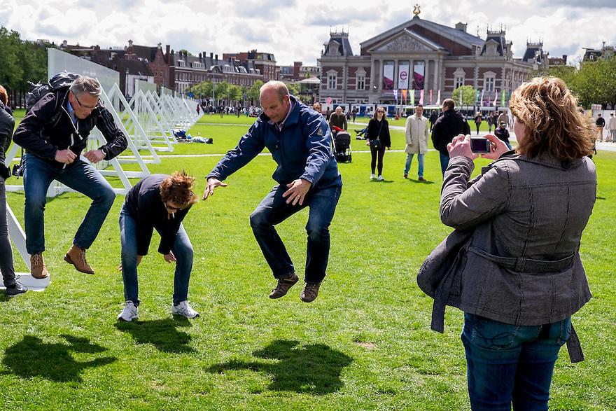 Nederland, Amsterdam, 30 mei 2015<br /> Groepje mensen doet een spel waarbij opdrachten uitgevoerd moeten worden om punten te krijgen. Een soort Wie is de Mol. Hier moet er gesprongen worden voor een foto. <br />  <br /> Foto: Michiel Wijnbergh