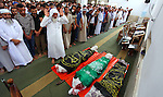 Palestinian mourners at a mosque pray over the bodies of Mousa Abu Muamer, 56, and his son, Saddam, 27, who were killed in an overnight Israeli missile strike at their house in the outskirts of the town of Khan Younis, southern Gaza Strip, Monday, July 14, 2014. Saddam's wife Hanadi, 27, was also killed in the attack. Photo by Ramadan El-Agha
