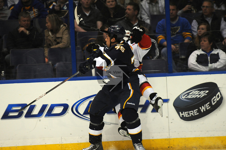 St. Louis Blues right wing Ryan Reaves (75) checks Calgary Flames defenseman Dennis Wideman (26) into the boards in the third period during a game between the Calgary Flames and the St. Louis Blues on Thursday April 25, 2013 at the Scottrade Center in downtown St. Louis.