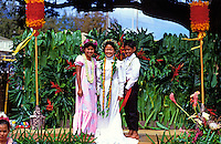 Three young schoolchildren celebrate Lei Day at Lili'oukalani School dressed in traditional aloha wear and standing on an outdoor stage flanked by colorful red and gold kahili standards.