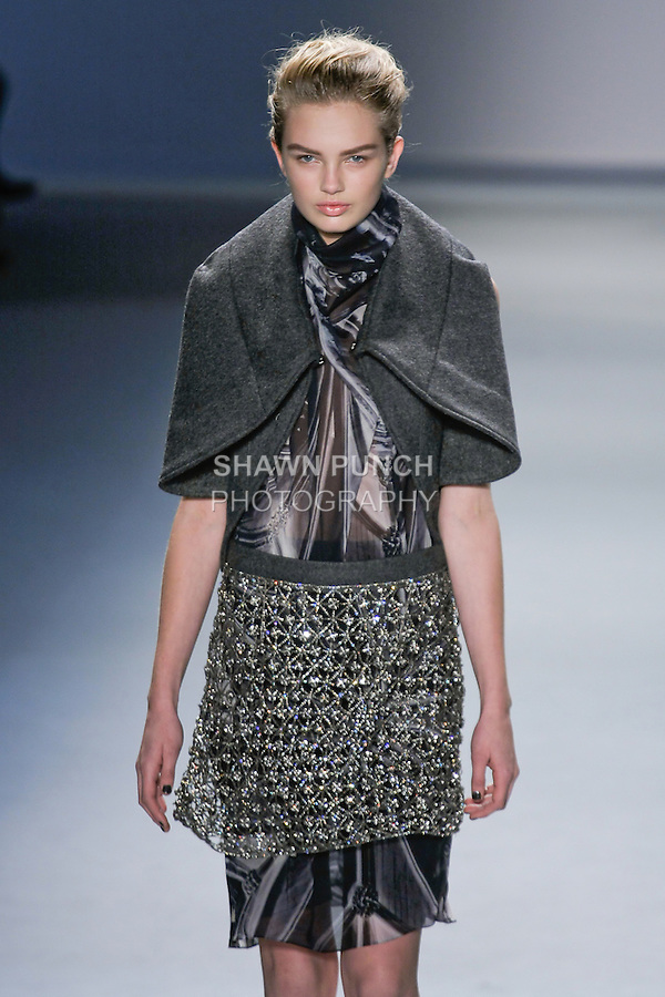 Romee Strijd walks runway in a charcoal melton cape over black vault print silk chiffon high neck sleeveless dress with crystal mesh skirt, from the Vera Wang Fall 2012 Vis-a-gris collection, during Mercedes-Benz Fashion Week Fall 2012 in New York.