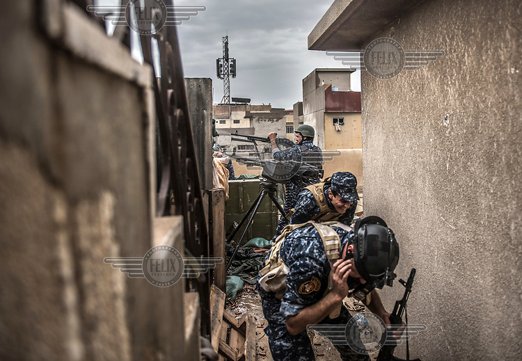 Two men take cover as a member of the Federal Police force fires at ISIS positions on the front line in the Bab Ajdiid neighbourhood of western Mosul.