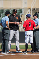Delmarva Shorebirds manager Ryan Minor (44) meets with first base umpire Zach Neff (left), home plate umpire Sam Burch (right),  and Tyler Sullivan (2) of the Kannapolis Intimidators prior to their game at Kannapolis Intimidators Stadium on July 2, 2017 in Kannapolis, North Carolina.  The Shorebirds defeated the Intimidators 5-4.  (Brian Westerholt/Four Seam Images)