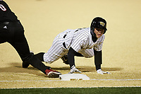 Derek Crum (20) of the Wake Forest Demon Deacons dives back into first base during the game against the Louisville Cardinals at David F. Couch Ballpark on March 6, 2020 in  Winston-Salem, North Carolina. The Cardinals defeated the Demon Deacons 4-1. (Brian Westerholt/Four Seam Images)