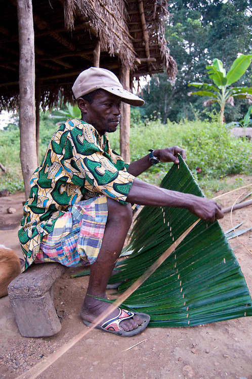 A man makes thatch roofing in the village of Lalehun