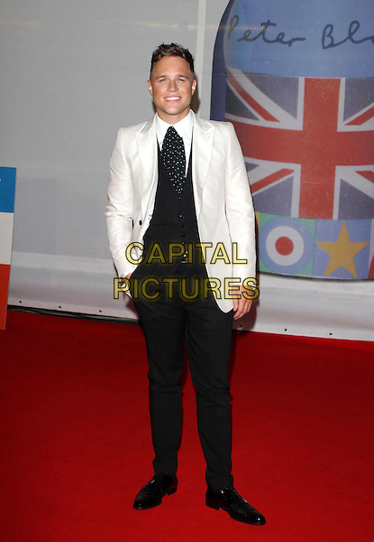 Olly Murs.The Brit Awards 2012 arrivals, O2 Greenwich, London, England 21st February 2012.Brits full length black suit waistcoat white jacket hand in pocket.CAP/ROS.©Steve Ross/Capital Pictures