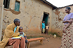 Emanuel Bizimungu  a community health worker in Rwanda, examines  a boy who he treated one month earlier for malaria The boy recovered after a few days on the drug Primo. They are  in Nyagakande village, near the Ruhunda health center in eastern Rwanda.  The patient's mother and three siblings look on.