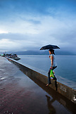 PHILIPPINES, Palawan, Puerto Princesa, woman steps off fo the sea wall in the City Port Area