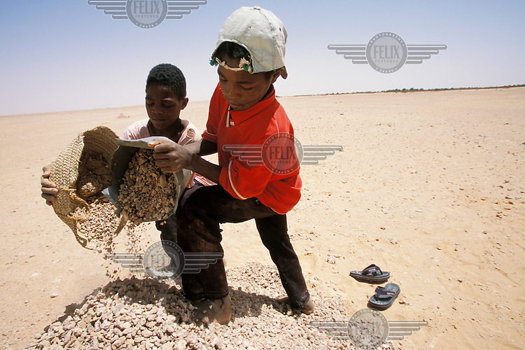 Children breaking up and moving stones for road construction.