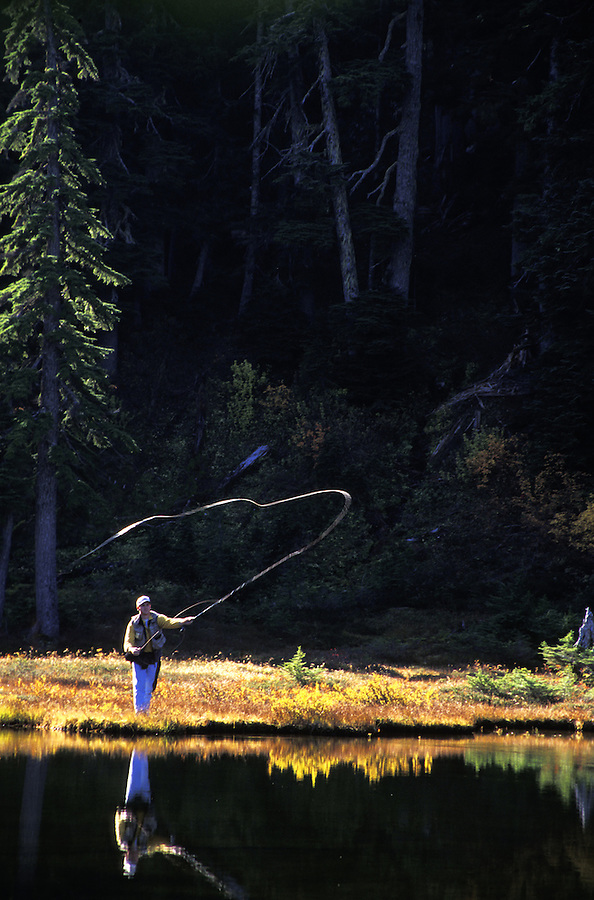 Man fly fishing subalpine lake, Grace Lakes, Stevens Pass, Cascade Mountains, Washington