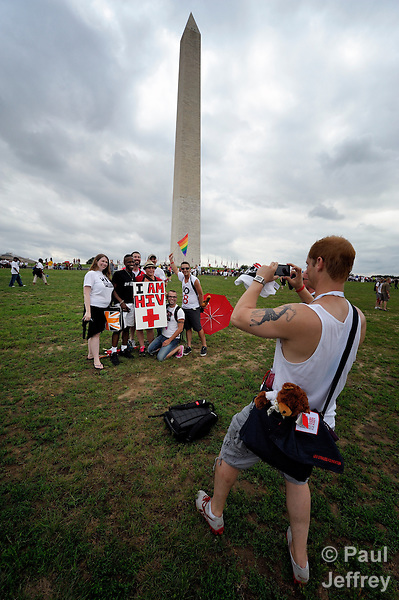 Participants photograph each other at a rally and march in the center of Washington, DC, on July 22, 2012, to demand that the U.S. and other governments keep their promises to fund global relief programs for those living with HIV and AIDS. The rally took place as more than 23,000 delegates gathered in the US capital city for the XIX International AIDS Conference. In the background is the Washington Monument.