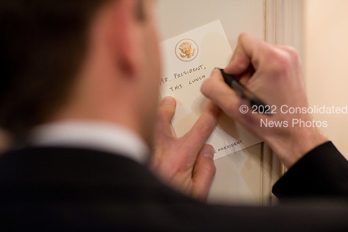 Deputy Director of Oval Office Operations Brian Mosteller writes a note to United States President Barack Obama during his CEO lunch in the Old Family Dining Room of the White House, Thursday, February 4, 2010..Mandatory Credit: Pete Souza - White House via CNP
