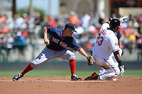 Boston Red Sox second baseman Brock Holt (26) attempts to tag Nelson Cruz (23) sliding in during a spring training game against the Baltimore Orioles on March 8, 2014 at Ed Smith Stadium in Sarasota, Florida.  Baltimore defeated Boston 7-3.  (Mike Janes/Four Seam Images)