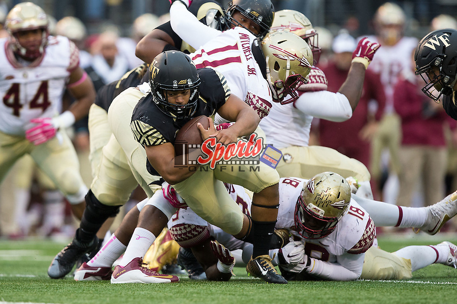 Matt Colburn (22) of the Wake Forest Demon Deacons falls forward for extra yards as he is tripped up by Ro'Derrick Hoskins (18) of the Florida State Seminoles during second half action at BB&T Field on October 3, 2015 in Winston-Salem, North Carolina.  The Seminoles defeated the Demon Deacons 24-16.   (Brian Westerholt/Sports On Film)