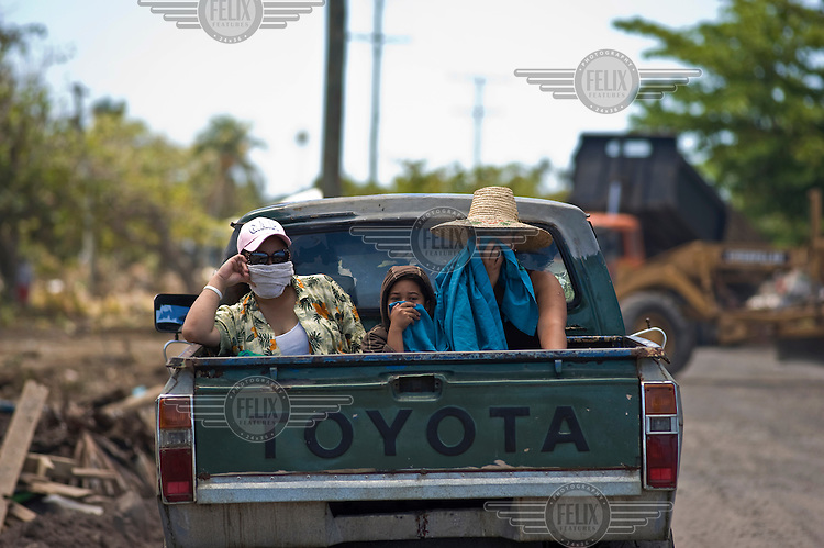 A family cover their faces from the stench of rotting fish and flesh as they leave the devastated Southern coast. More than 170 people died when a tsunami triggered by an 8.3 magnitude earthquake hit Samoa and neighbouring Pacific islands on 29/09/2009. Samoa (formerly known as Western Samoa)..