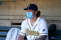 Savannah Bananas Dan Oberst (28) wears a mask while sitting in the dugout before a Collegiate Summer League game against the Macon Bacon on July 15, 2020 at Grayson Stadium in Savannah, Georgia.  (Mike Janes/Four Seam Images)