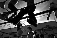 "Mexican kids play on the ropes of the ring before a fight at a local arena in Mexico City, Mexico, 28 May 2011. Lucha libre, literally ""free fight"" in Spanish, is a unique Mexican sporting event and cultural phenomenon. Based on aerial acrobatics, rapid holds and the use of mysterious masks, Lucha libre features the wrestlers as fictional characters (Good vs. Evil). Women wrestlers, known as luchadoras, often wear bright shiny leotards, black pantyhose or other provocative costumes. Given the popularity of Lucha libre in Mexico, many wrestlers have reached the cult status, showing up in movies or TV shows. However, almost all female fighters are amateur part-time wrestlers or housewives. Passing through the dirty remote areas in the peripheries, listening to the obscene screams from the mainly male audience, these no-name luchadoras fight straight on the street and charge about 10 US dollars for a show. Still, most of the young luchadoras train hard and wrestle virtually anywhere dreaming to escape from the poverty and to become a star worshipped by the modern Mexican society."