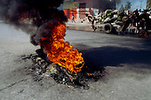 Port-au-Prince, Haiti<br /> November 25, 1987<br /> <br /> The street burning of a suspected ton-ton-macoute prior to elections being held on November 29th, the first attempt at a democratic election in Haiti. It was unsuccessful as 34 people were killed at a polling station and elections were moved up to February 1988.<br /> <br /> Leslie Fran&ccedil;ois Manigat won the election with many political parties boycotting. He had military backing but once in office he sought greater control over the military in an effort, to fight corruption. Manigat's government was overthrown by General Henri Namphy within months.