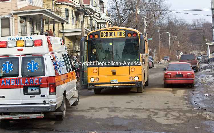 WATERBURY, CT - 11 FEBRUARY 2009 -021109JT02-<br /> A Waterbury police officer takes down information on a school bus that hit a parked car on Lounsbury Street near Baldwin Street on Wednesday afternoon in Waterbury.<br /> Josalee Thrift / Republican-American