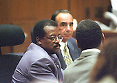 Lead defense attorney Johnnie L. Cochran, Jr., left, confers with his client, former NFL star running back O.J. Simpson, right, during his trial for the murder of his former wife, Nicole Brown Simpson and a friend of hers, restaurant waiter, Ron Goldman in Los Angeles County Superior Court in Los Angeles, California on July 13, 1995.  Defense attorney Robert Shapiro looks on at center.<br /> Credit: Steve Grayson / Pool via CNP