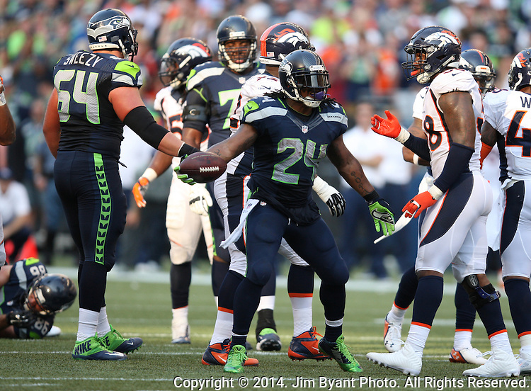 Seattle Seahawks running back Marshawn Lynch (24) dances In front of Denver Broncos safety Quinton carter (38) after picking up a seven-yard gain in overtime at CenturyLink Field in Seattle, Washington on September 21, 2014.   Lynch ran for 88 yards and scored two touchdowns in the Seahawks 26-20 overtime win over the Broncos.  Providing blocking against the Broncos defenders is tackle Russell Okung (76)  and tight end Zach Miller (86)  ©2014. Jim Bryant Photo. All rights Reserved.