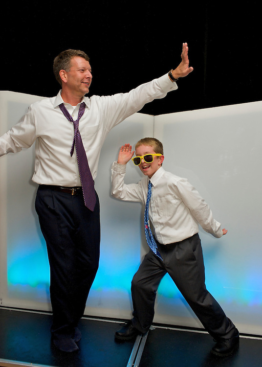 Father and son hamming it up at a Bar Mitzvah party.