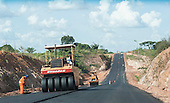 Altamira, Para State, Brazil. Road building work with road rollers and construction workers.