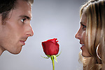 Young handsome man with a red rose facing a beautiful young woman