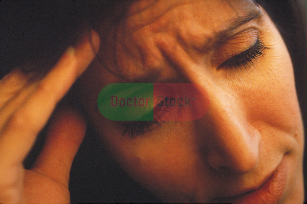 close-up of woman with headache rubbing forehead