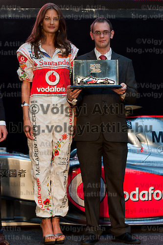 Fashion model Reka Ebergenyi (L) presents McLaren team drivers' new traditional Hungarian decorated overall designed by Istvan Kalmar (R) during the annual Hugo Boss party just prior to the Hungarian F1 Grand Prix in Budapest, Hungary. Thursday, 28. July 2011. ATTILA VOLGYI