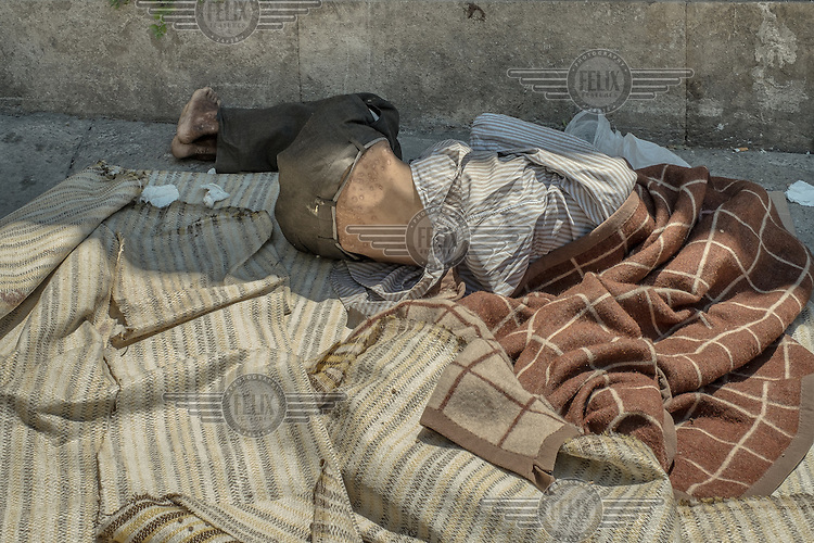 A drug user lies, wrapped in dirty blankets, on the ground.