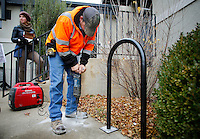 NWA Media/DAVID GOTTSCHALK - 12/3/14 - Lee Porter, left,  sustainability project coordinator with the city of Fayetteville, works with Aaron Wood, lead maintenance worker, as he drills bolt holes for a  bicycle rack Wednesday December 3, 2014 behind the Development Service Building in Fayetteville. Twenty one new bicycle racks were installed in the downtown area paid for by benefitting city departments and a city fund specifically designated for bicycle rack installation.