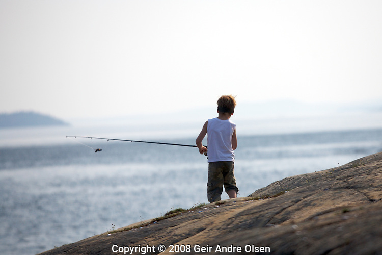 Boy fishing and haveing fun in the summer at Filtvet, sothern Norway