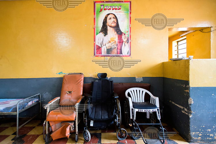 A religious poster and wheelchairs in the infirmary of the Accra Psychiatric Hospital.