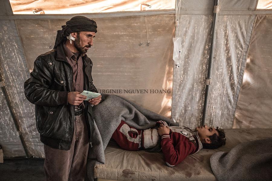IRAK, Khazer: A father stays next to his son who's waiting for his transfer to the hospital of Erbil. They have been injured by a suicide car bombing in their village near Mossul, the 5th december 2016. <br /> <br /> IRAK, Khazer: Un p&egrave;re et son fils attendent leur transfert vers un hopital d'Erbil dans le camp de d&eacute;plac&eacute;s de Khazer. Ils ont &eacute;t&eacute; bless&eacute;s par une attaque suicide de Daesh dans leur village &agrave; proximit&eacute; de Mossoul, le 5 d&eacute;cembre 2016.