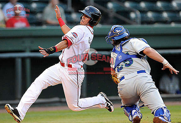 Jesus Loya (17) of the Greenville Drive slides around the late tag of catcher Cam Gallagher (25) of the Lexington Legends and scores the first run in a game on Monday, August 19, 2013, at Fluor Field at the West End in Greenville, South Carolina. (Tom Priddy/Four Seam Images)