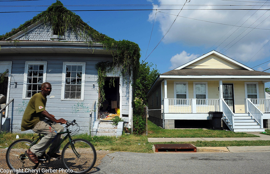 A man rides his bicycle past a Katrina-blighted house and one that has been rebuilt in the Seventh Ward.