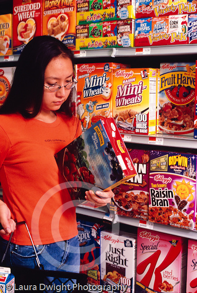 College student female shopping at supermarket, reading label on cereal package