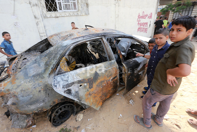 Palestinian children gather around a burnt-out car after explosions destroyed five cars in Gaza City July 19, 2015. The spokesman for Gaza's interior ministry said that a number of cars belonging to Palestinian factions were blown up by vandals and the security services started to investigate the incident. Photo by Mohammed Asad