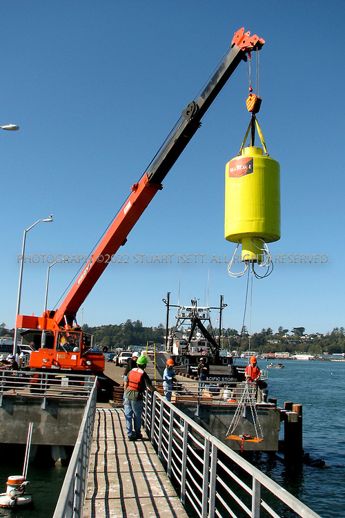 10/12/2007--Newport, OR, USA..Photograph courtesy of Oregon State University..Oregon State University researchers  prepare a wave energy buoy for deployment off the coast of Oregon in the Pacific Ocean...After waiting out a week of stormy seas, Oregon State University researchers launched the first test run of their wave energy buoy Saturday, October 12th. The buoy is the fifth prototype Oregon State University engineering professor Annette von Jouanne's team has built, and the first tested by OSU in open seas. Previous testing has been done in labs and in Yaquina Bay, von Jouanne said...The buoy was towed to a point about 21/2 miles offshore from Newport,.and returned later in the day. ..Photograph courtesy of Oregon State University