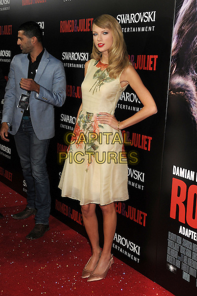Taylor Swift<br /> &quot;Romeo &amp; Juliet&quot; Los Angeles Premiere held at Arclight Cinemas, Hollywood, California, USA.<br /> September 24th, 2013<br /> full length floral hand on hip yellow red green print dress sleeveless <br /> CAP/ADM/BP<br /> &copy;Byron Purvis/AdMedia/Capital Pictures