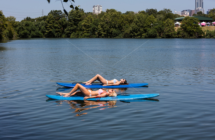 Two attractive, fit women sun tan on SUP stand-up paddle boards on Lady Bird Town Lake at Festival Beach.