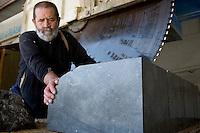 Pierre Gavazzi, stonemason (tailleur de pierre) at work in his workshop at Annot quarry, Annot, France, 26 April 2010